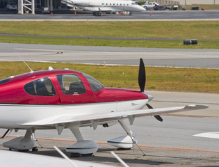 Red and White Prop Plane with Jet in Background