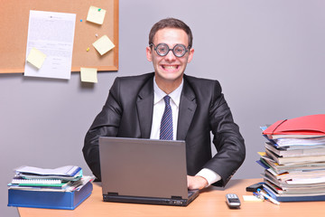 Nerdy businessman working on a laptop in the office