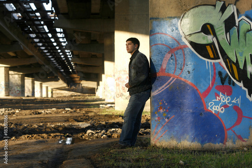 Young handsome man leaning against the bridge column