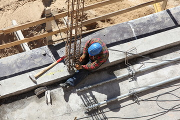 Worker working on a construction site column.