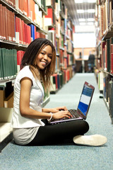 Teenage black girl sitting in the library with her laptop
