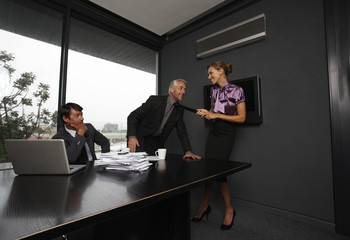 Businesswoman pulling businessman's tie