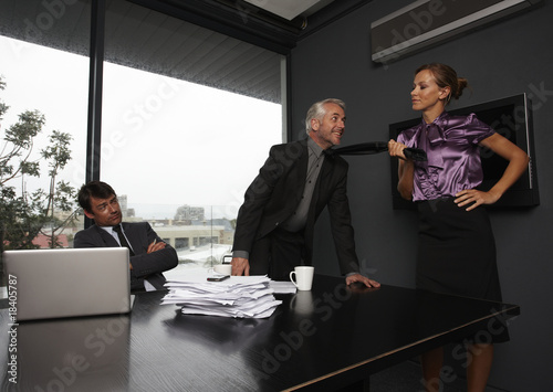 Woman pulling businesman tie