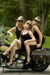 three sexy middle age women onclassic vintage motorcycle