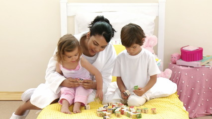 Mother and children playing toy cubes on the bed