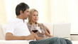 Couple using a laptop and drinking wine