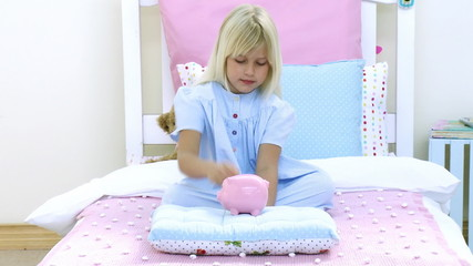 Little girl saving money in a piggy bank
