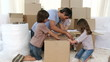 Parents and children moving house packing boxes