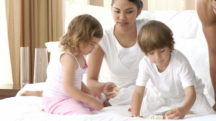 Parents playing toy cubes with their children in bedroom