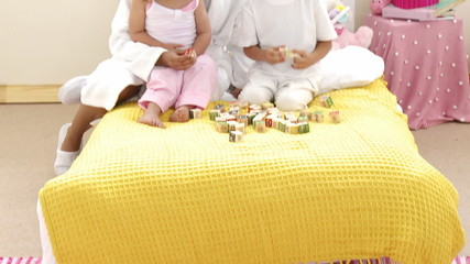 Mother playing with her daughter toy cubes in bedroom