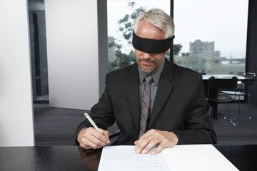 Man signing a contract with eyes closed