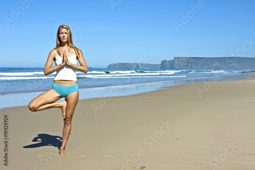 Young fit woman doing exercises on the beach