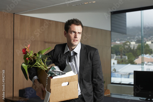 Sad businessman with his personal belongings