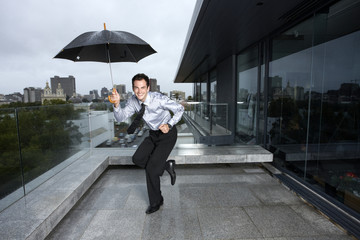 Businessman dancing in the rain