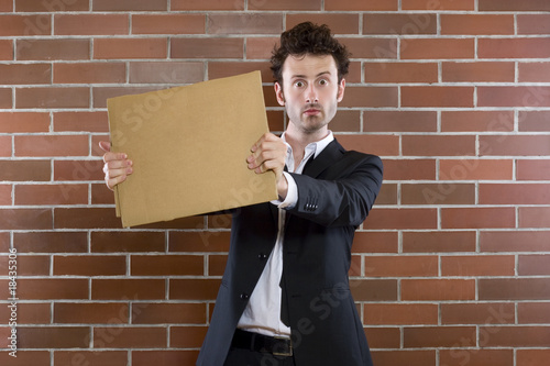 poor unshaved businessman pleads with a blank sign