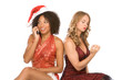 two Christmas women one talking on cell phone