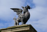 statue of Welsh dragon carrying hand of man poster