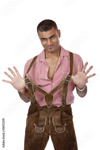 Sexy man holds Oktoberfest leather trousers braces - Lederhose