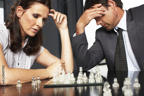 Businessman and businesswoman playing chess