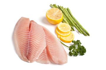 raw filleted tilapia with asparagus, parsley and lemon on white
