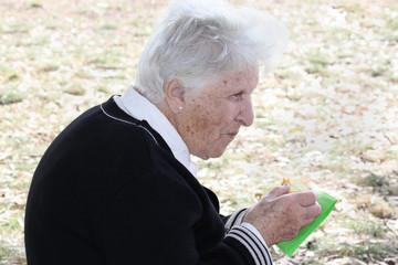 old woman eating cake