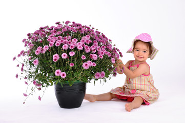 Cute baby playing with huge pot of flowers