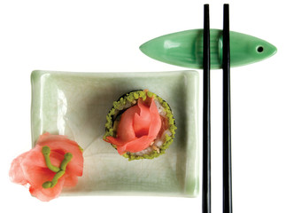 Chopsticks and plate with sushi on white background