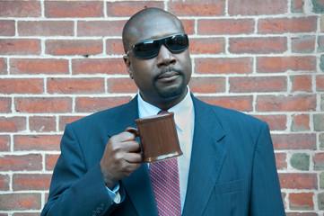 Businesman Holding Coffee Mug By Brick Wall