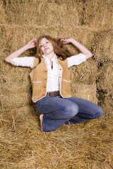 Woman posing by hay stack