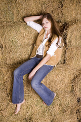 woman posing sitting on haystack