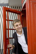 man inside traditional English red telephone box