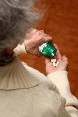 donna anziana versa pillole nella mano