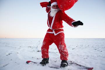 Weihnachtsmann balanciert beim Snowboarding