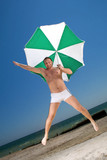 Bizarre young man with umbrella on a beach poster