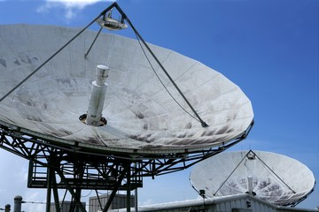 Parabolic satellite dish receiver over blue sky