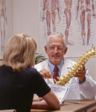 chiropractic doctor showing spine to a patient poster