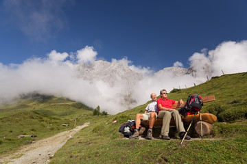 happy couple relaxing on bench in mountains