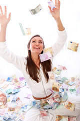 Junge Frau sitzt glücklich im Geldregen