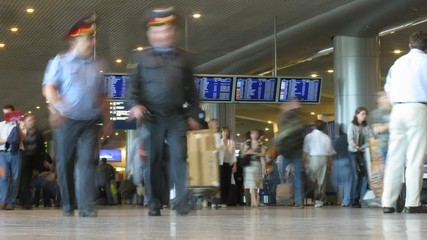 Passengers with luggage and board in hall of the airport