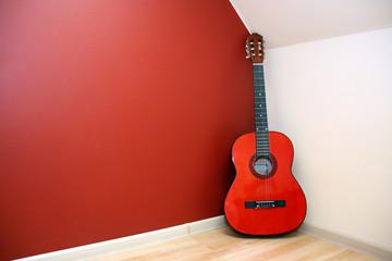acoustic guitar in room corner