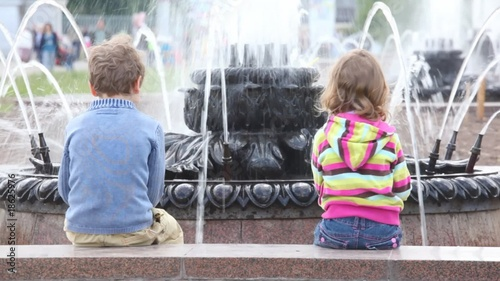 boy and girl seating at fountain