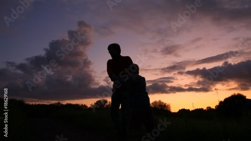 father rotating with son on sunset background