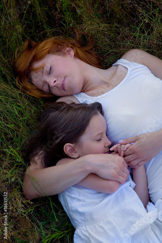 Young mother and daughter sleeping on grass