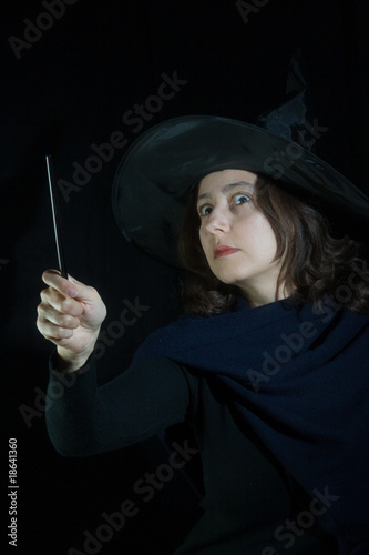woman with magic wand on black background