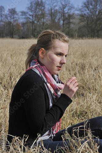 Teenager sitzt auf der Wiese