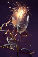 Champagnerglaeser auf lila Untergrund mit Tischfeuerwerk