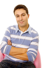 Portrait of a young casual man, seated on a pink small sofa, iso