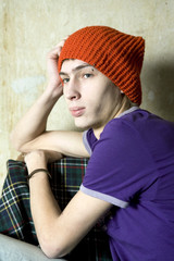 portrait of serious young man in red hat sitting at old wall