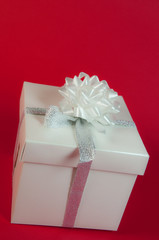 pacco regalo con nastro argentato su fondo rosso