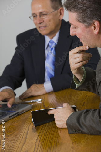 Busineesmen discussing laptop data